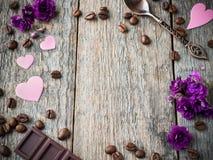 Garneringar för valentindag skyler över brister hjärtor, violets och chokladkaffe på lantlig träbakgrund Royaltyfri Foto