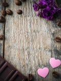 Garneringar för valentindag skyler över brister hjärtor, violets och chokladkaffe på lantlig träbakgrund Arkivbilder