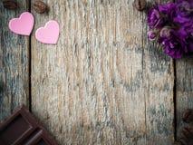Garneringar för valentindag skyler över brister hjärtor, violets och chokladkaffe på lantlig träbakgrund Arkivfoto