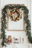 Garneringar på julspisen i form av ljusstakar, jul krans och fotoramen, tappningdocka arkivfoton