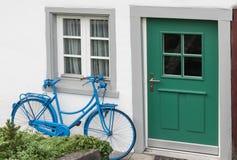 Garneringen av tappningcykeln och vitbyggnad med den gröna dörren Den gamla blåa retro cykeln och ferie inhyser bakgrund Fotografering för Bildbyråer