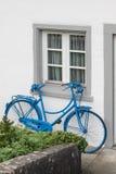 Garneringen av tappningcykeln och vitbyggnad med den gröna dörren Den gamla blåa retro cykeln och ferie inhyser bakgrund Royaltyfria Bilder