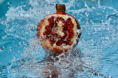 Garnet. Juicy pomegranate in a spray of water, fresh juicy fruits, health and vitamins, juicy colors grenade lying on the mirror Royalty Free Stock Image
