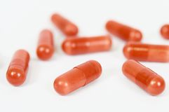 Garnets capsules on white background. Garnet capsules isolated and in macro view to make illustrations on the use of medicines and health Royalty Free Stock Images