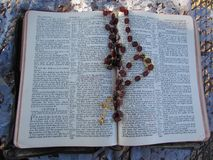 Garnet and Gold Rosary Beads Draped over Open Bible with Diffused Sunlight Background. Rosary beads draped over an open Bible taken in my garden with a lace stock image