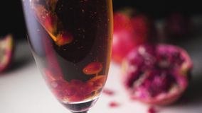 Garnet grains fall into champagne slow mo stock video