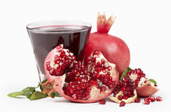 Garnet juice in a glass and pomegranate on the Stock Image