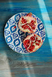 Garnet on plate with blue and white pattern Royalty Free Stock Photography
