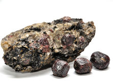Garnets. Three garnets and containing rock royalty free stock photo