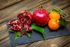 Garnets with mandarins with green leaves. An open red ripe juicy pomegranate near the ripe, yellow manadrinas with green leaves lie on a black board made of Royalty Free Stock Photo