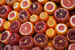 Garnets, mandarins and oranges. Ripe juicy garnets, mandarins and oranges are cut on sale at the counter of a fruit shop on the street of Istanbul Stock Images