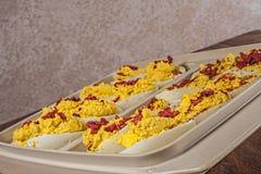 Garnished deviled ägg, behållaren, skärbräda Royaltyfri Foto