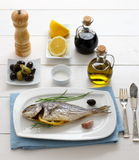 Garnished grilled sea bream with olives, lemon Royalty Free Stock Photography