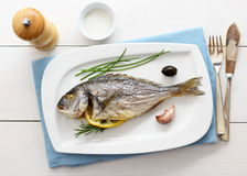 Garnished grilled whole sea bream with lemon Royalty Free Stock Photo
