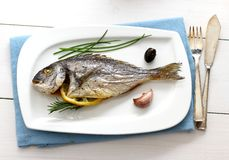 Garnished grilled whole sea bream with olives Stock Photo
