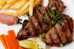 Garnished plate of grilled steak meat Royalty Free Stock Photography
