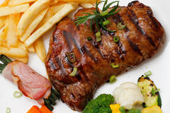 Garnished plate of grilled steak meat Royalty Free Stock Image