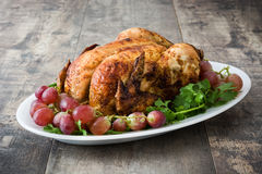 Garnished roasted turkey with grapes and herbs on a wooden table. Delicious garnished roasted turkey with grapes and herbs on a wooden table royalty free stock image