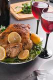Garnished roasted turkey on holiday decorated table with glasses of red wine Stock Image