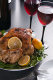 Garnished roasted turkey on holiday decorated table with glasses of red wine Royalty Free Stock Image