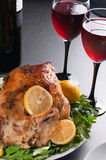 Garnished roasted turkey on holiday decorated table with glasses of red wine Stock Images