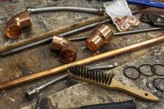 Garnitures de cuivre de tuyauterie sur un établi occupé de plombiers photographie stock libre de droits