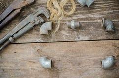 Garnitures de tuyauterie de clé à tube sur le conseil en bois image libre de droits