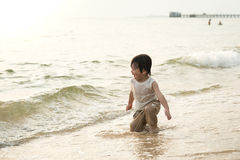 Garçon asiatique mignon jouant sur la plage Image stock