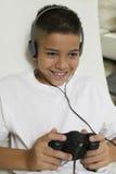 Garçon avec des écouteurs jouant le jeu vidéo Photographie stock libre de droits