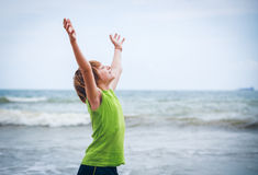 Garçon avec les mains augmentées sur le bord de la mer Photo stock