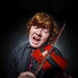Garçon couvert de taches de rousseur de rouge-cheveux jouant le violon Image stock