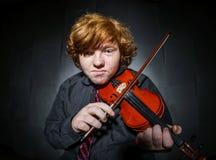 Garçon couvert de taches de rousseur de rouge-cheveux jouant le violon Photos stock
