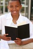 Garçon d'adolescent d'Afro-américain affichant un livre Photographie stock