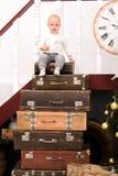 Garçon d'enfant en bas âge sur la pile des valises Image libre de droits