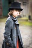 Garçon dans le long manteau et le chapeau supérieur Image libre de droits