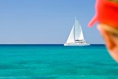 Garçon dans un capuchon rouge ; ooking sur le catamaran blanc Photo libre de droits