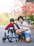 Garçon de l'adolescence avec le petit frère handicapé dans le marcheur Photographie stock libre de droits
