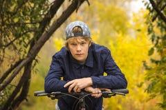 Garçon de l'adolescence se reposant sur une barre de poignée de bicyclette Photographie stock