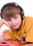 Garçon de sourire écoutant la musique Photographie stock libre de droits