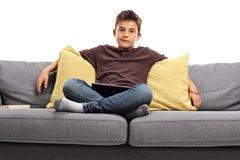 Garçon ennuyé s'asseyant sur un sofa Photos libres de droits