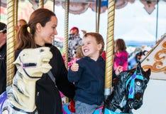 Garçon et mère sur le carrousel souriant à l'un l'autre Photos stock