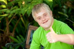 Garçon handicapé mignon affichant des pouces vers le haut à l'extérieur. Photos libres de droits