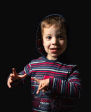 Garçon heureux avec le hoodie se tenant au-dessus du fond noir Image stock