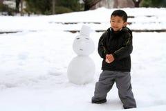 Garçon japonais ayant le combat et le bonhomme de neige de boule de neige Image libre de droits