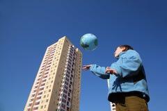 Garçon jouant avec le ballon sous la forme du globe Photographie stock libre de droits