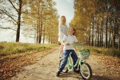 Garçon jouant avec une fille dans la route de campagne d'automne Image stock