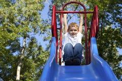 Garçon jouant sur une glissière au stationnement Image libre de droits