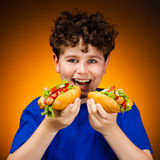 Garçon mangeant de grands sandwichs Photographie stock libre de droits