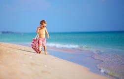 Garçon mignon de petit enfant marchant le bord de la mer, vacances d'été Image stock