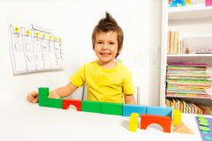 Garçon mignon riant mettant des blocs dans l'ordre Image stock